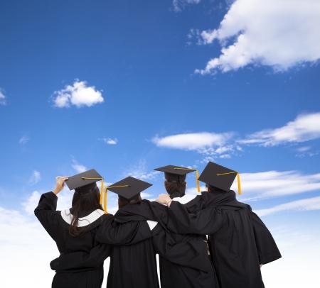 fondo de graduacion: cuatro estudiantes de postgrado que buscan en el cielo Foto de archivo