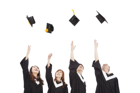 gelukkige jonge afgestudeerde studenten groep gooien van de hoed Stockfoto
