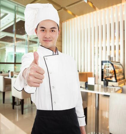 young chef with thumb up gesture in the restaurant photo