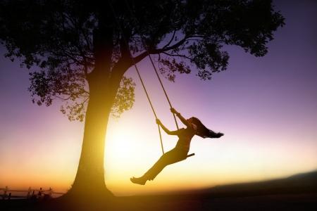 silhouette de jeune femme heureuse sur une balançoire avec un fond coucher de soleil Banque d'images