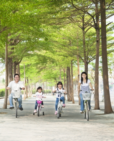 asian family fun: happy family riding bicycle in the park