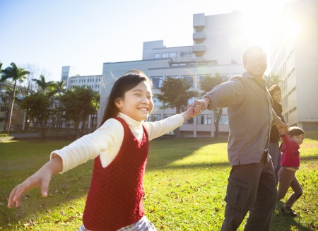 enfants qui rient: heureuse petite fille en famille dans le parc Banque d'images
