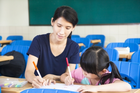 asian teacher: mother teaching little girl drawing picture in the classroom Stock Photo