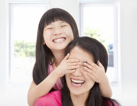 asian mother and daughter: happy little girl cover her mother eyes for fun Stock Photo