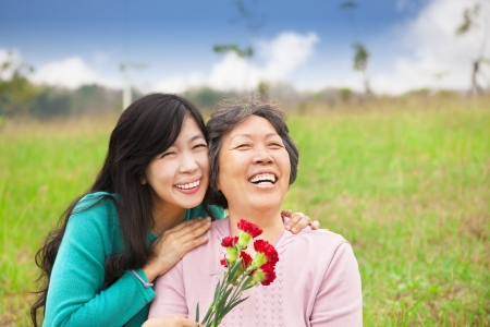 mother and daughter: Smiling daughter and her mother with carnation flower on the grass field Stock Photo