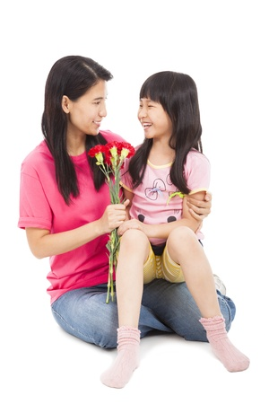 Little girl giving carnation flowers  on mother's day photo