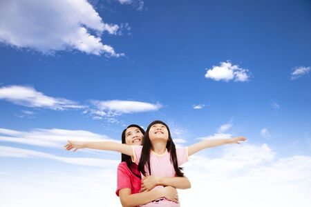 happy little girl and mother watching the sky photo
