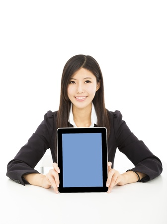 smiling young businesswoman showing tablet pc on the desk photo