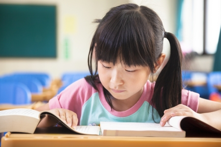 concentrate: little girl study alone in the classroom Stock Photo