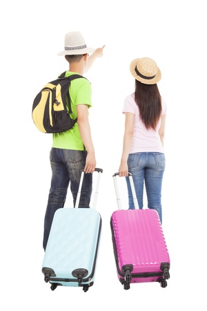 young couple tourist with travel suitcase and pointing something photo