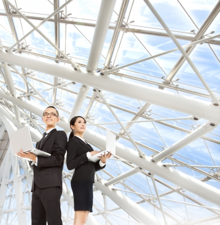 젊은 비즈니스 남자와 여자는 노트북을 들고 현대 사무실에 서