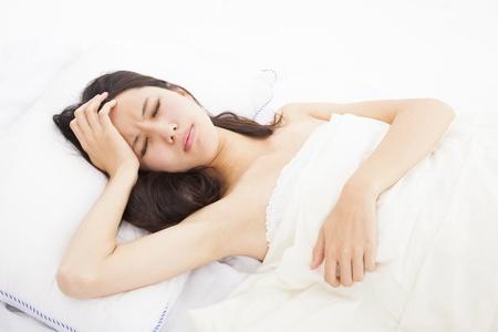 dolor de cabeza: mujer enferma en la cama, toc�ndose la cabeza
