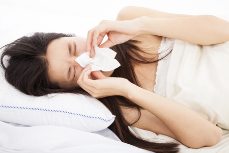 running nose: young Woman with flu and laying in bed