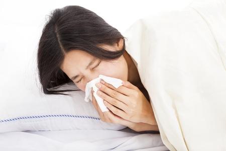 estornudo: joven mujer con el enfermo y en la cama