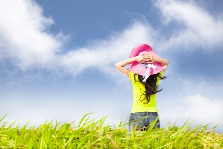 Mujer joven de pie en el campo de hierba mirando las nubes
