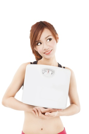 young woman holding weight scale and looking something photo
