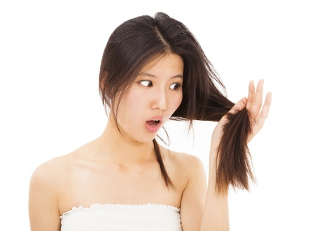shocked woman watching the damage hair and splitting ends photo