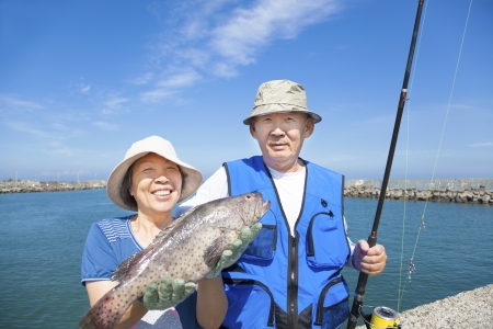 happy senior couple go fishing and showing big fish photo