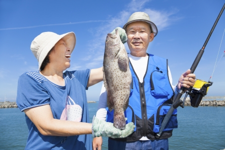 happy asian senior couple fishing and showing big grouper Stock Photo - 19938652