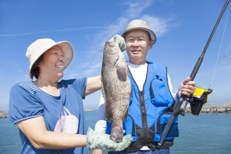 asian senior couple fishing and showing big grouper photo