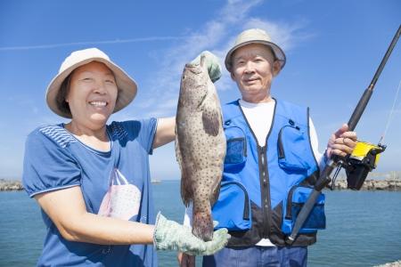 fisher animal: happy senior couple fishing and showing big grouper Stock Photo