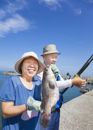 happy senior couple fishing and showing big grouper fish photo