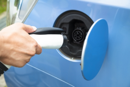 electric automobile: hand holding plug for Charging of an electric car Stock Photo