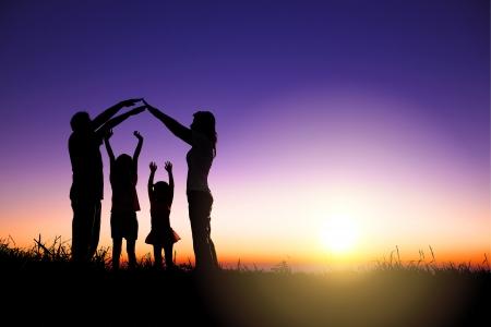 행복한 가족은 일출 배경으로 언덕에 집 기호를 만드는
