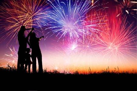 night fireworks: happy family standing on the hill and watching the fireworks  Stock Photo