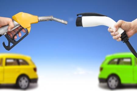 電気自動車とガソリン車のコンセプトです。燃料補給のためのガスのポンプと電源コネクタを持っている手します。 写真素材