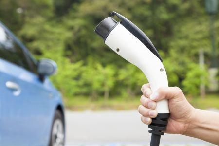 electric automobile: hand holding plug in connector for Charging electric car Stock Photo