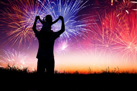 night fireworks: father with child standing on the hill and watching the fireworks