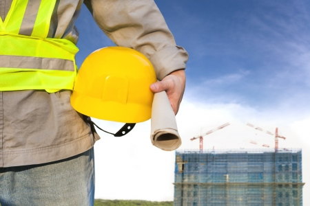 helmet construction: Construction building with worker holding hat