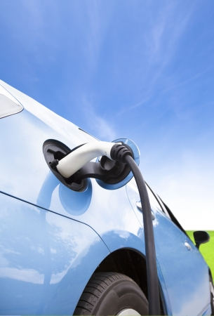 electric automobile: Charging of an electric car with cloud background Stock Photo