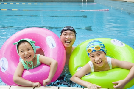 asian sport: happy father and daughter in the swimming pool