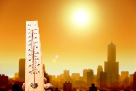 Hitzewelle in der Stadt und Hand zeigt Thermometer für hohe Temperaturen Standard-Bild - 20681099