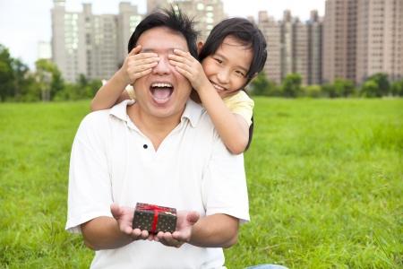 dando la mano: padre sorprendido con caja de regalo de la niña para el día de padre Foto de archivo
