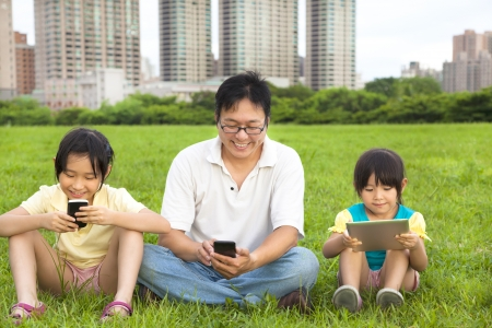 mobile communication: happy family using smart phone and tablet pc outdoor