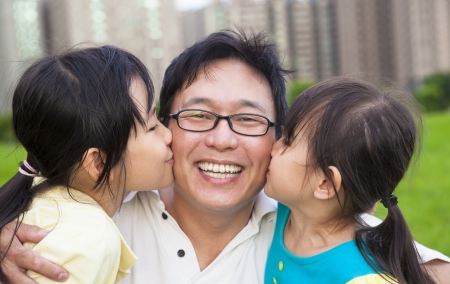 parenting: happy little girls kissing their father