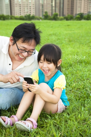 telephone together: happy father and little girl watching the smart phone