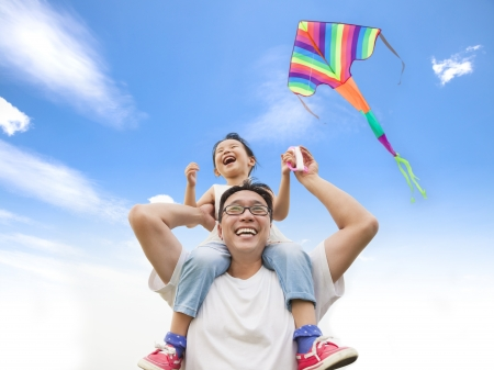 happy little girl on his father shoulder with colorful kite Фото со стока