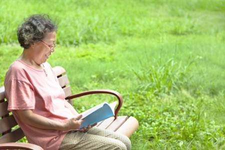 happy senior woman sitting on  bench and reading a book photo