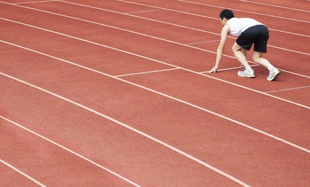 young athlete is at the start of the line at the stadium photo