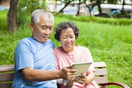 a year older: happy seniors couple with tablet pc in the park