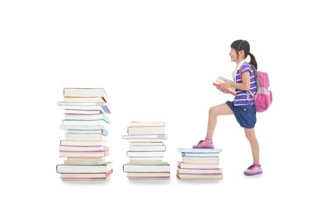 happy little girl with backpack walking to the top of books photo