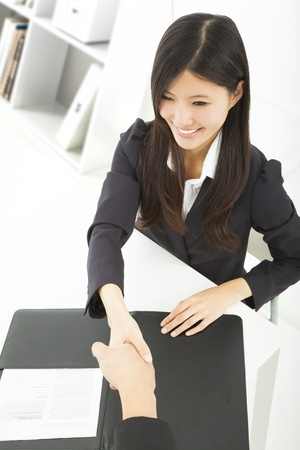 smiling businesswoman handshaking with businessman in the office photo