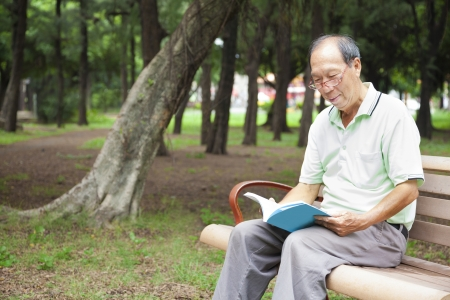 happy senior man sitting on  bench and reading  book photo