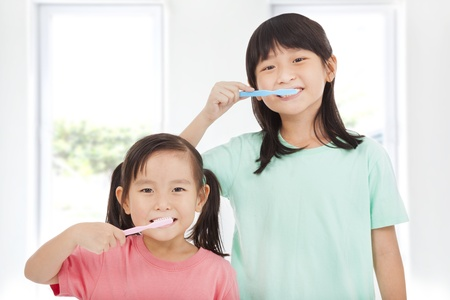 tooth cleaning: two happy little girls brushing her teeth
