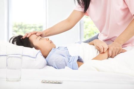 bambini tristi: Madre di controllo della temperatura della figlia malata a mano