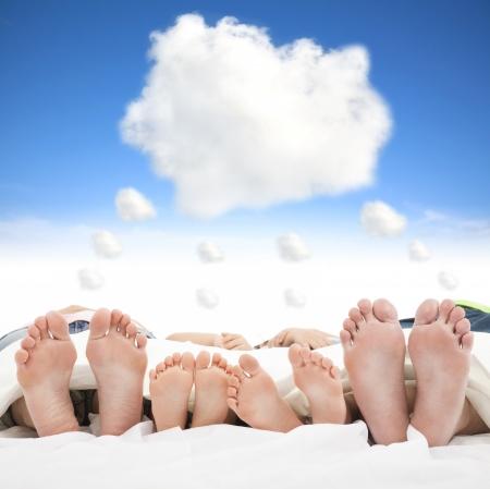 Familie schläft auf dem Bett mit Traum-Cloud-Konzept